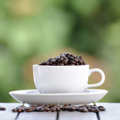 Coffee seeds with white cup and nice bokeh blur background.