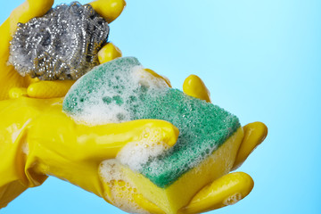 Woman's hands in gloves with sponge