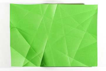 Green folded sheet of paper isolated on the bright background
