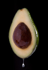 Avocado with olive oil on black background