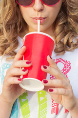 young girl in sunglasses drinking coke through a straw