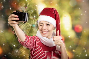 girl in a cap of Santa Claus with a camera in hand