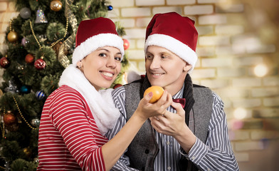 young couple in Santa caps. man and woman at christmasм