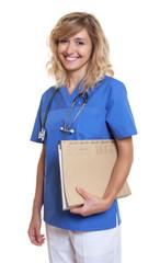 Lachende Krankenschwester mit blonden Haaren und Akte