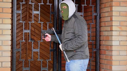 Robber with crowbar near the gates