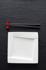 Chopsticks and white plate on black rock