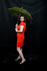 lass with an umbrella stands under rain