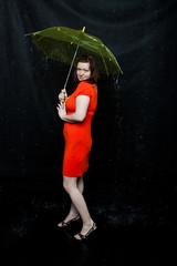 lass with an umbrella stands under rain
