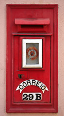 Portuguese red mail box on pink wall.