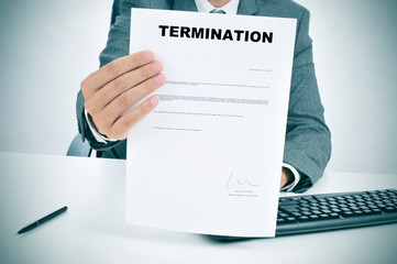 man in suit showing a figured signed termination document