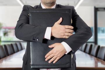 Uomo in ufficio con valigetta stretta