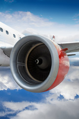 Airplane With Red Engine Flying Through Clouds