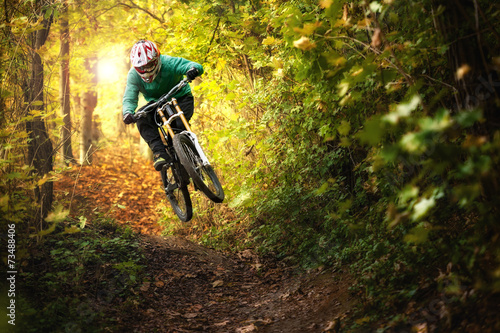 Mountainbiker rides in autumn forest