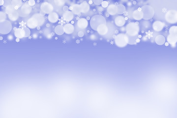 The white blurred balls and snowflakes on a blue background