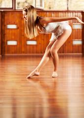 Young ballerina posing in a dance studio, in profile