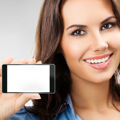 Businesswoman showing blank cellphone, on grey