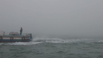 Fisherman on motor boat in bad weather