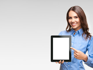 Businesswoman showing blank tablet pc, on grey
