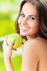 Young woman with green apple, outdoors