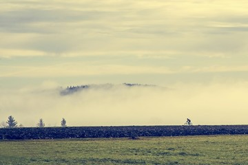 lone cyclist in a misty landscape