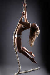 Curly-haired young woman hanging on rope