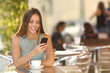 Girl texting on the phone in a restaurant - 73493482
