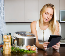 woman  reading ereader and cooking with  crockpot