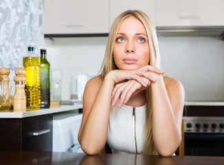 Sad young woman sitting at kitchen