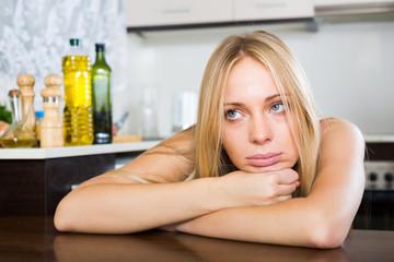 Sad young woman sitting at kitchen