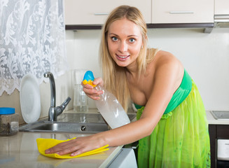 blonde woman cleaning  furniture and smiling