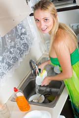 housewife washing plates with sponge
