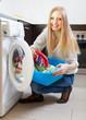 Happy woman loading the washing machine