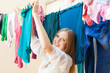 Positive long-haired housewife drying clothes