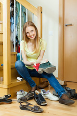Happy blonde girl cleaning shoes