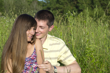 Young couple in love with wildflowers on the grass
