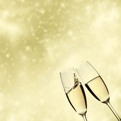 Toasting with champagne glasses on sparkling holiday background