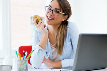 Pretty young woman eating an apple in her office.