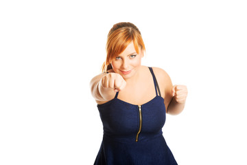 Overweight woman with her fists up