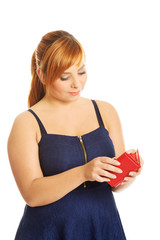 Overweight woman holding an empty wallet