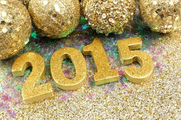 2015 New Years Eve golden numbers on confetti with shiny baubles