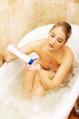 Beautiful woman squeezing shampoo