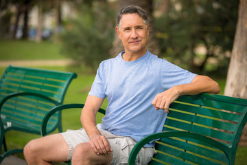 Elder man sitting at a bench in the park