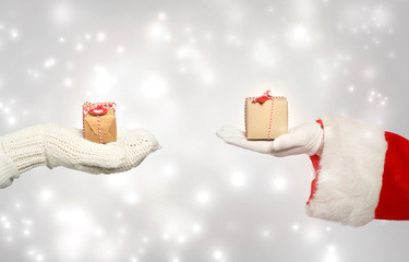 Santa and winter gloves hand holding gift boxes