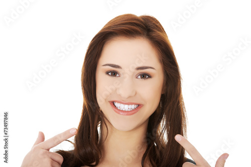 canvas print picture Young woman showing her teeth