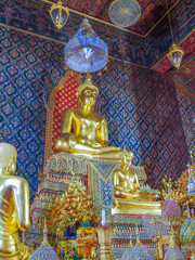 Gold pained Buddha statues in the temple with mural painting.