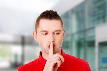 Man gesturing to be quiet