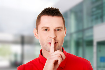 Man gesturing to be quiet