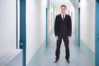 Happy Businessman Standing In Office Corridor