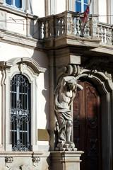 Detail of an baroque atlant of Palazzo Litta facade, Milan
