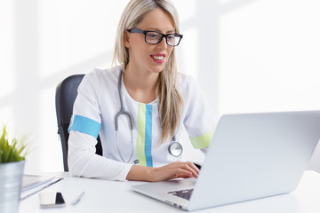Woman doctor working with computer in the office